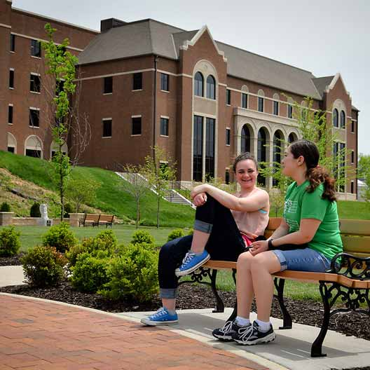 Students relax in Raven Memorial Park, with Westerman Hall in the background