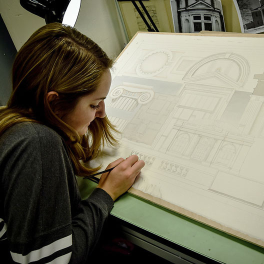 A student at a drafting table in Architecture class