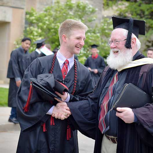A graduate laughs with a professor as they prepare for Commencement