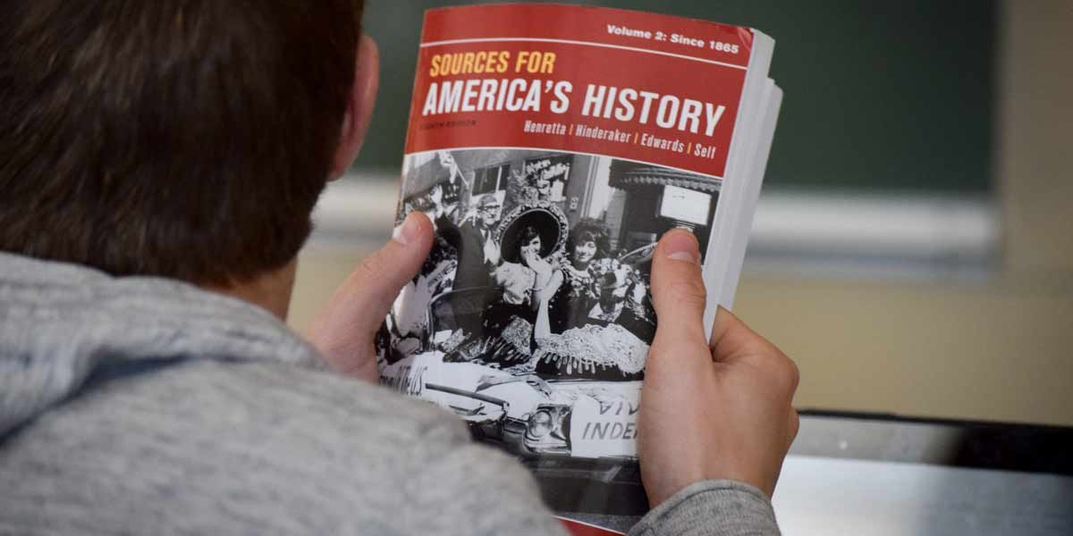 A student holds a history textbook in class
