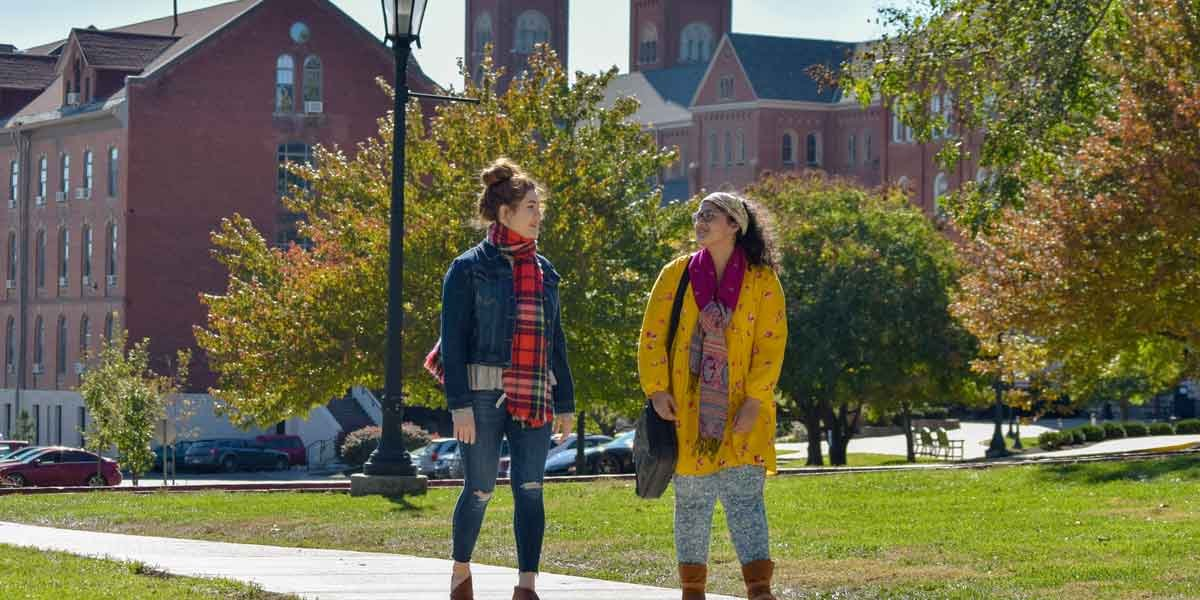 Two students walk together on campus