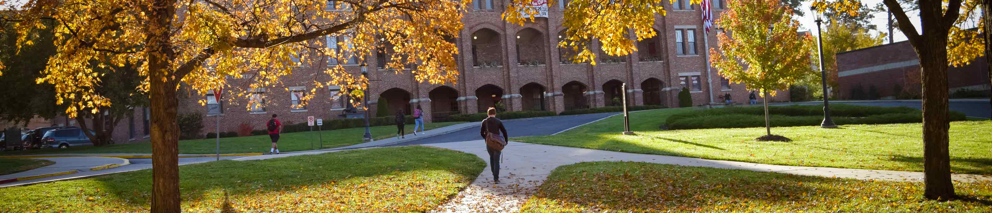 A student walks on an autumn Benedictine College campus