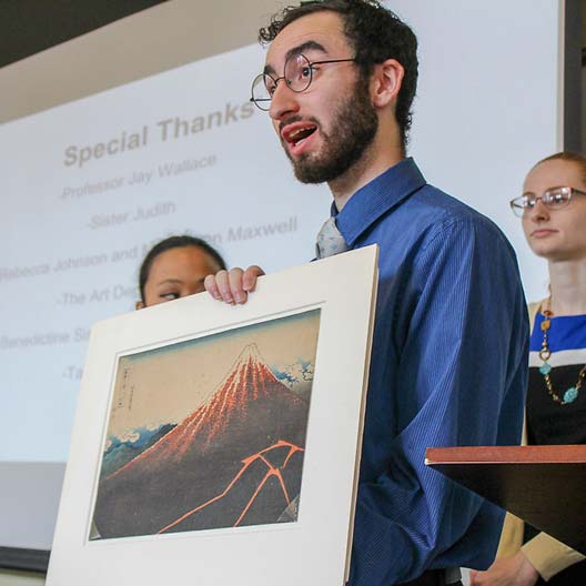 A student shows a painting during a Discovery Day presentation