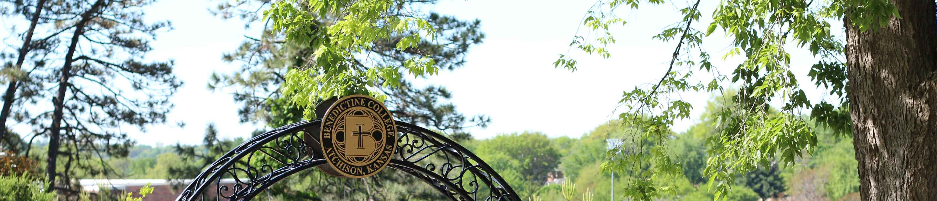 The Benedictine College Seal set atop the entry archway to Mary's Grotto
