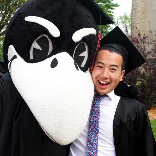 A graduate posing with Rocky the Raven
