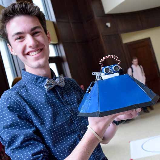 Student poses with his battle bot during Discovery Day