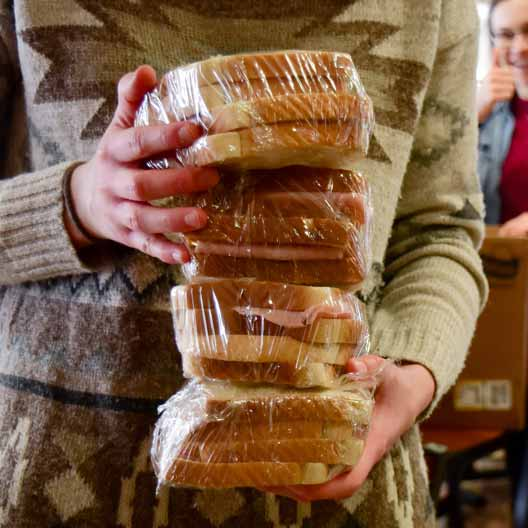 A person holds a stack of sandwiches
