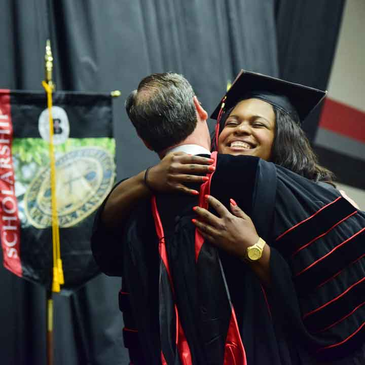 A graduate hugs President Minnis at Commencement
