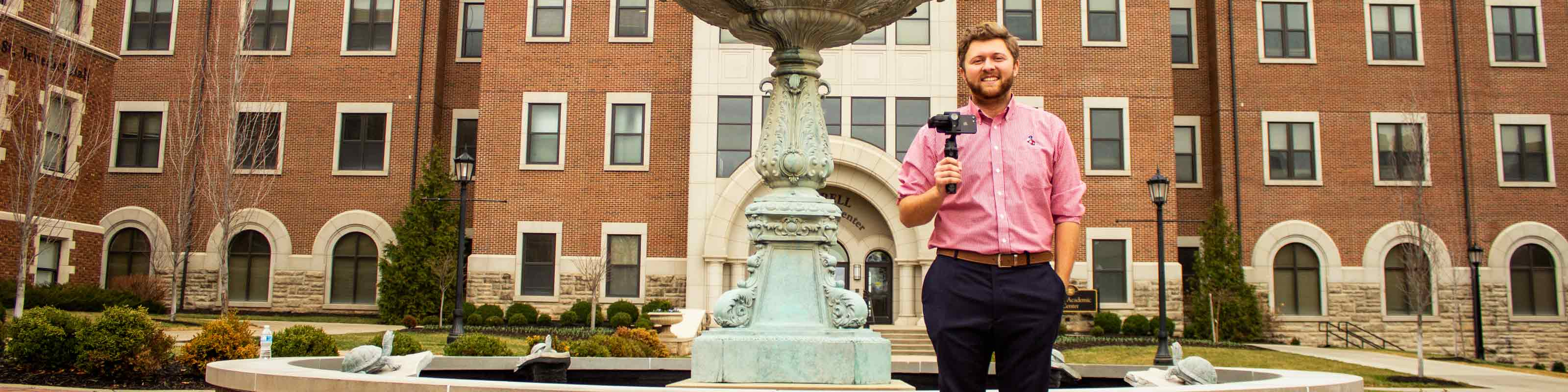 An Admission Counselor stands next to Our Lady of Grace Fountain holding a smartphone in a gimble