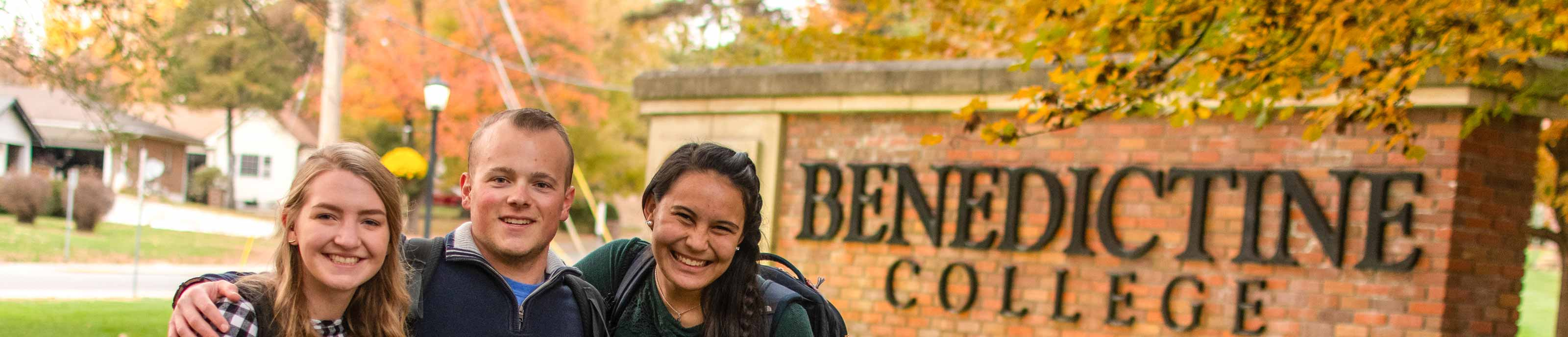 Three students pose for a photo in front of the Benedictine College entrance sign