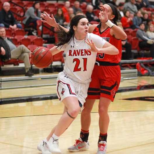 Lady Ravens basketball player pushing past a defender to score
