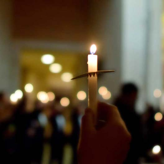 A hand holds a candle during a prayer service