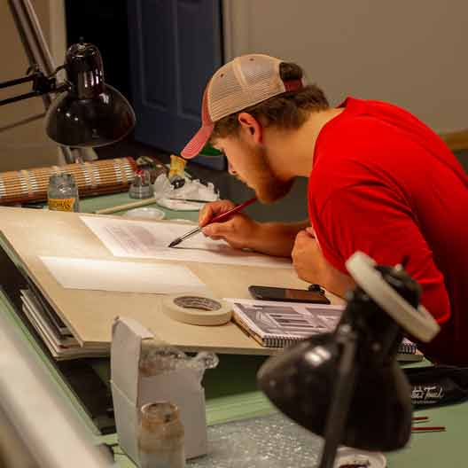 A student works at a drafting table