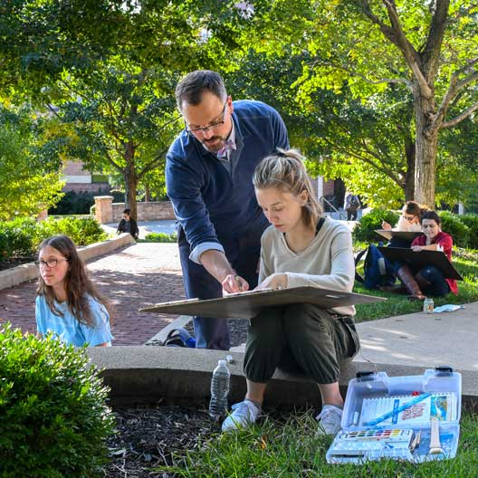 John Haigh assists a student in an outdoors Architecture class