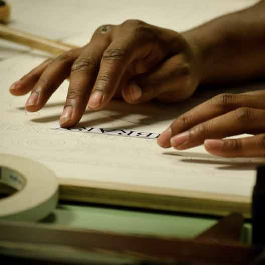 A student's hands working at a drafting table in Architecture class