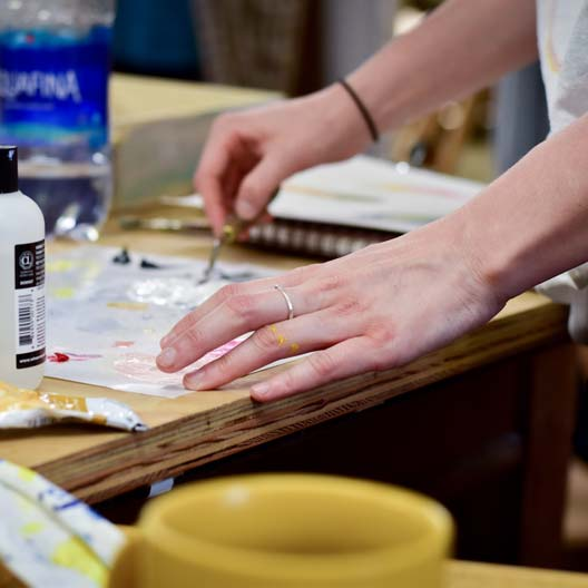 A student's hands work with art supplies at a table