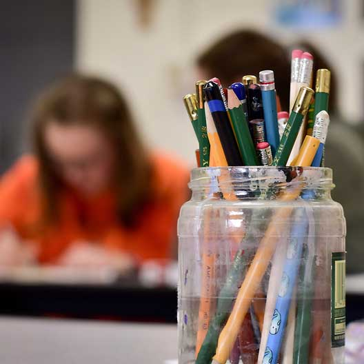 A jar of pencils, with a students at work in the background