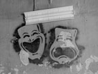 Comedy and tragedy masks spray-painted onto a ceiling, with a florescent light set above them.