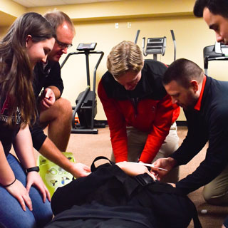 Health, Wellness, and Exercise Science Students practice emergency care, with a fellow student posing on a stretcher