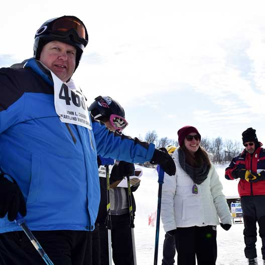 A Special Olympics athlete in ski gear, with a Benedictine College student volunteer nearby
