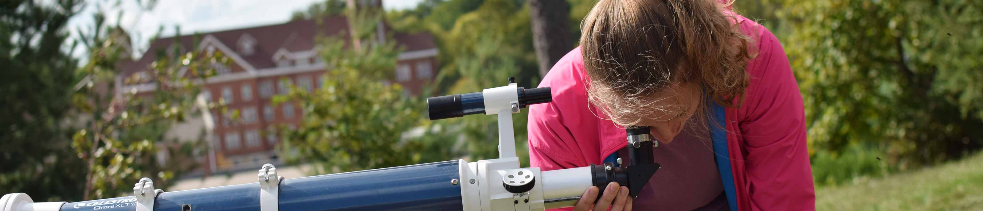 A student looks through a telescope in Astronomy class