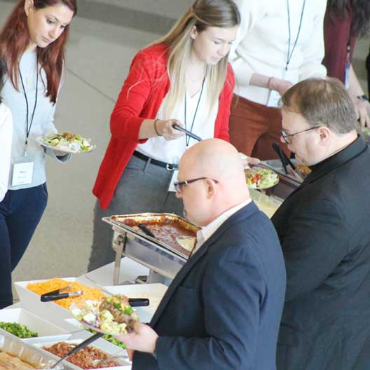 MEDCON Conference attendees serving themselves food in a line.
