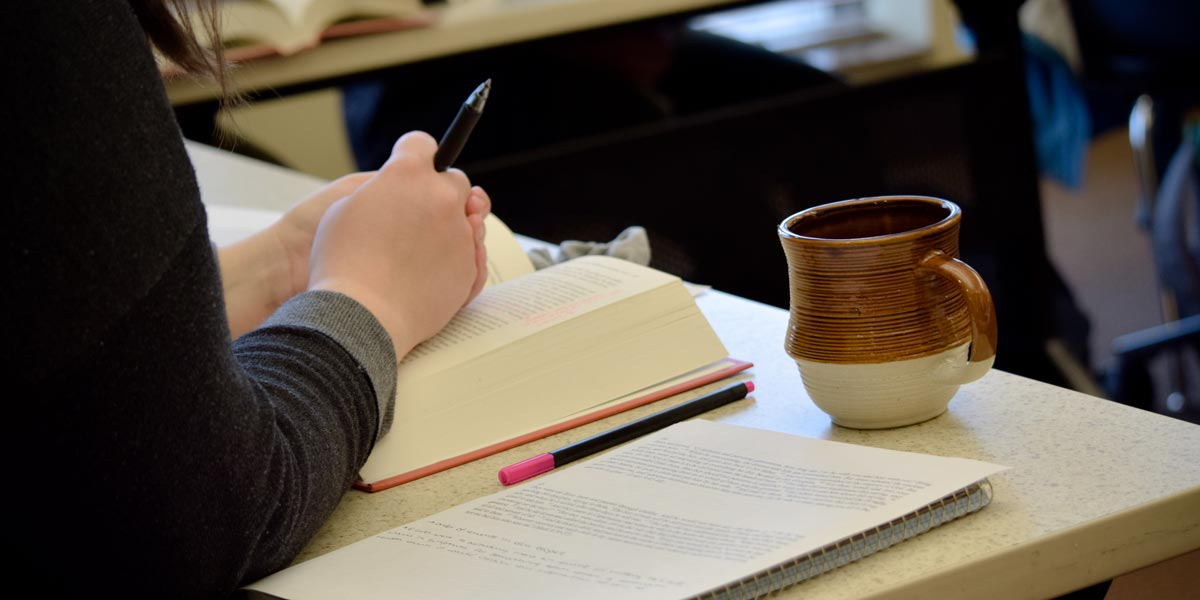 Student sitting at a desk with a book, notes, and coffee mug