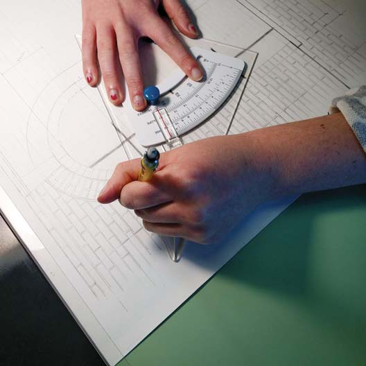 Close-up of hands drafting architecture designs