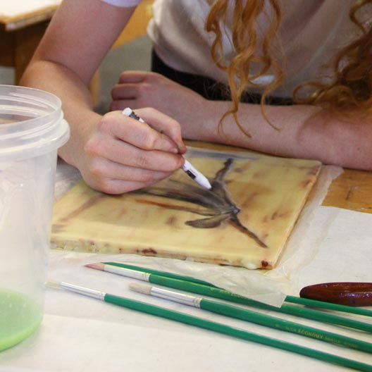 A student's hands painting at a table