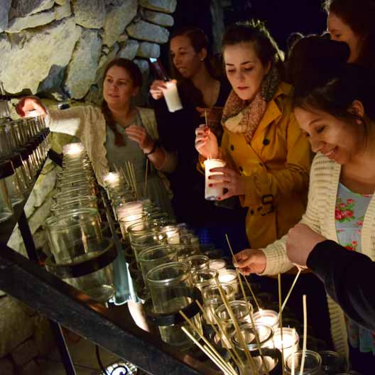 Students lighting candles at Mary's Grotto