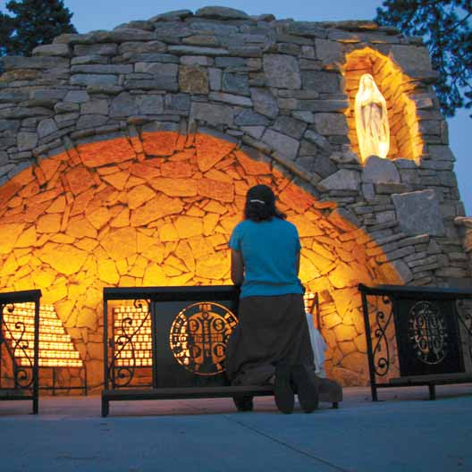 A woman prays at Mary's Grotto