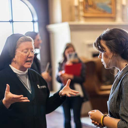 A religious sister in conversation with a student