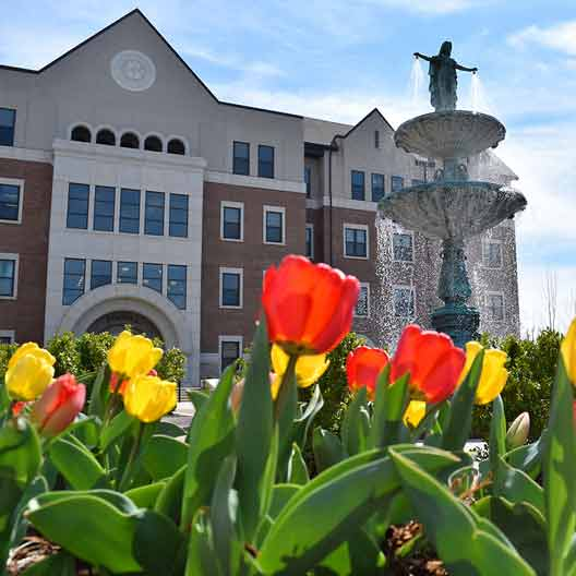 The facade of the Ferrell Academic Center with Our Lady of Grace Fountain in the foreground