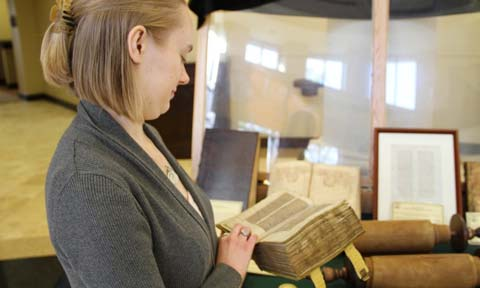 Student examining an old tome during the Wisdom of the Ages exhibit