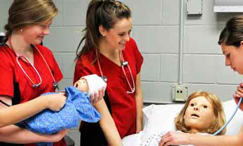 Nursing students work with a birth simulator
