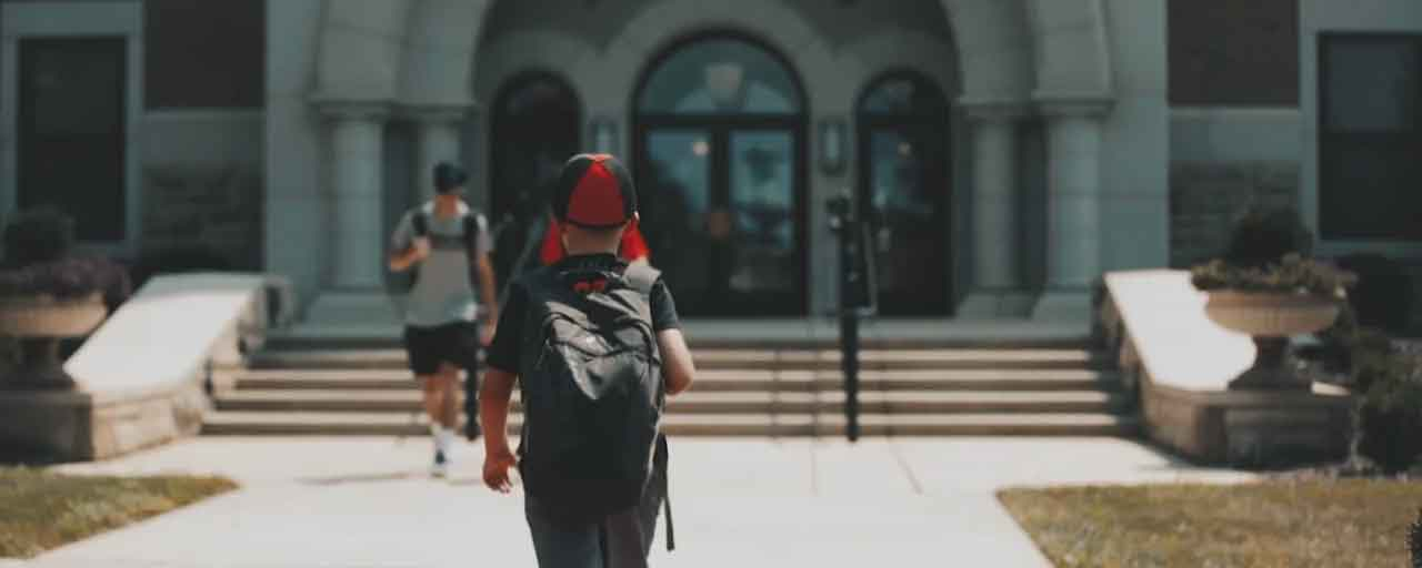 A young boy wearing a beanie walks towards the steps of the Ferrell Academic Center