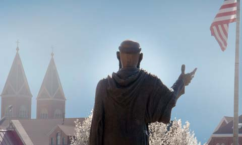 An image of the statue of St. Benedict with the American flag and the spires of St. Benedict Church