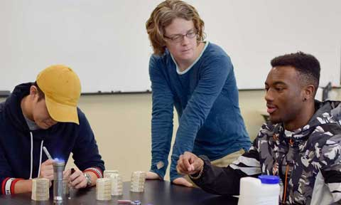 Dr. Virginia Winder working with students at a table in Biology class