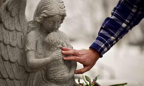 A student's hand touching a statue of a child held by an angel