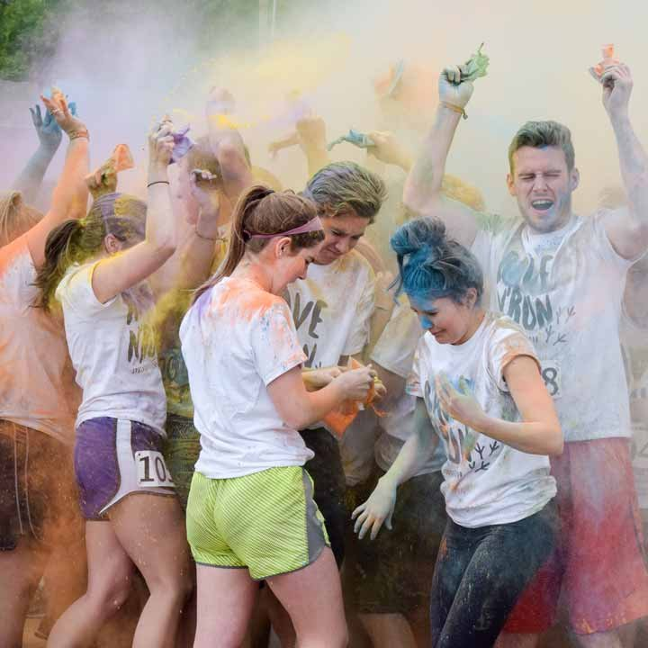 Students having fun in a cloud of brightly-colored powder at the Color Run