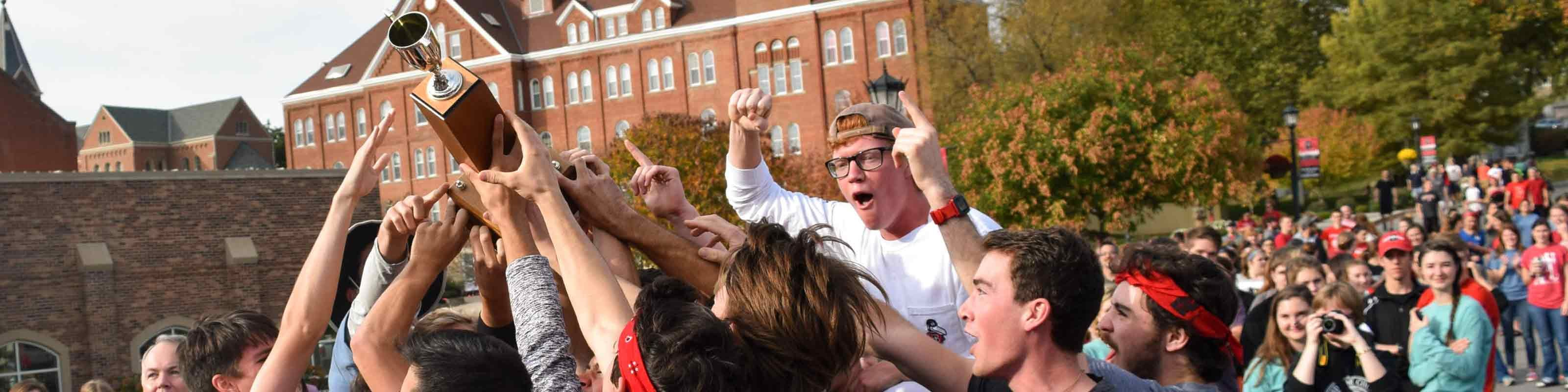 A group holds up a trophy at the end of the Homecoming Bed Races